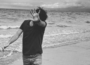 monochrome photo of person standing on seashore